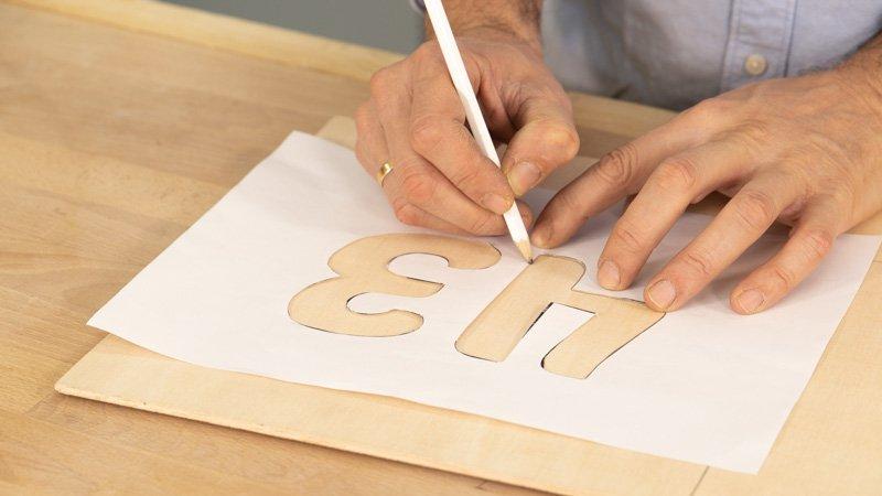 Lápiz trazando los números en un tablero de madera