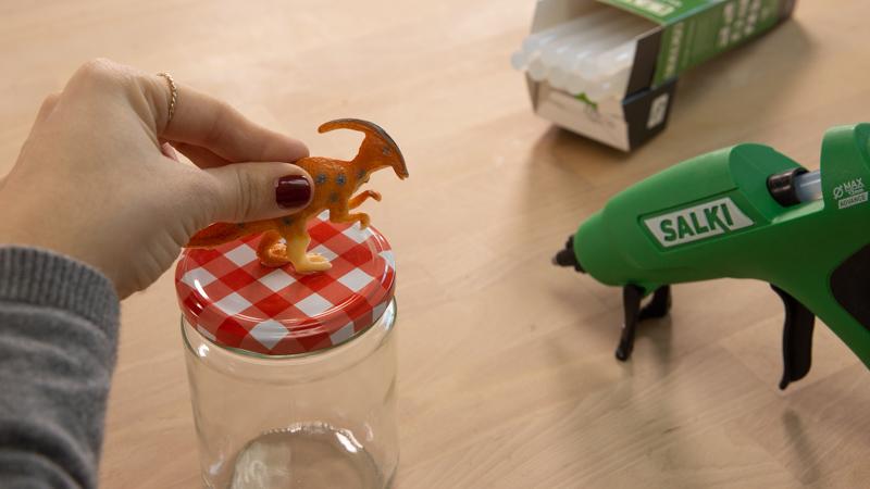 Pegado de los dinosaurios de plástico sobre las tapas de los botes