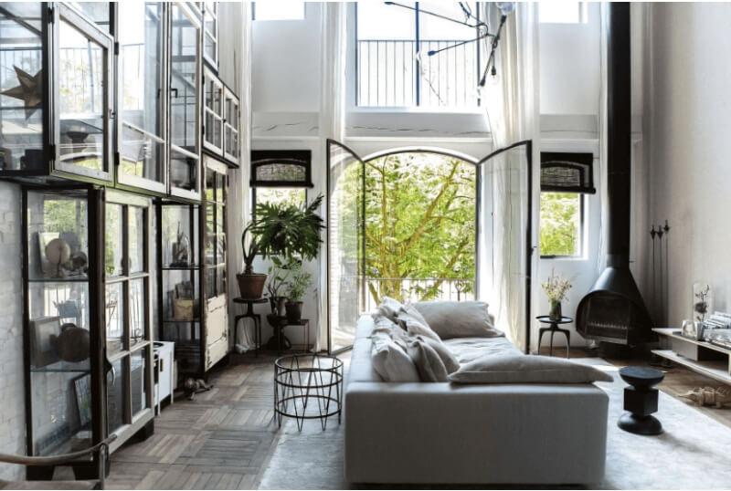Decoración industrial en un espacio amplio con suelos de madera techos altos y muebles de hierro forjado y cristal.