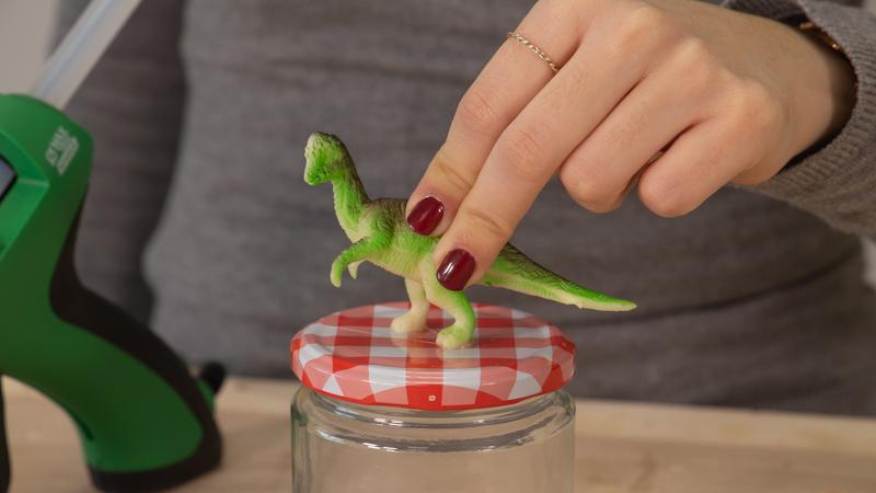 Fijación de los dinosaurios de plástico en las tapas de los botes