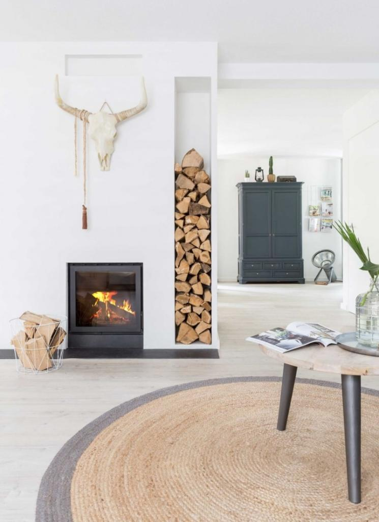 Salón con estilo industrial y mezcla boho rústico decorado con chimenea y troncos