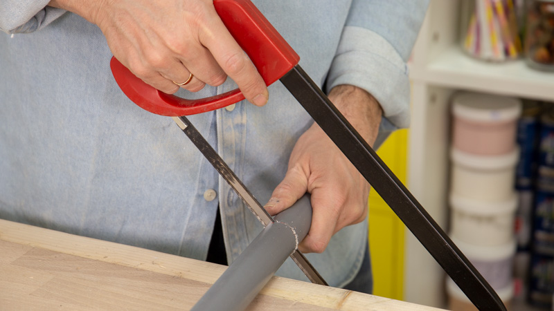Sierra de arco cortando tubos de PVC para crear el manillar
