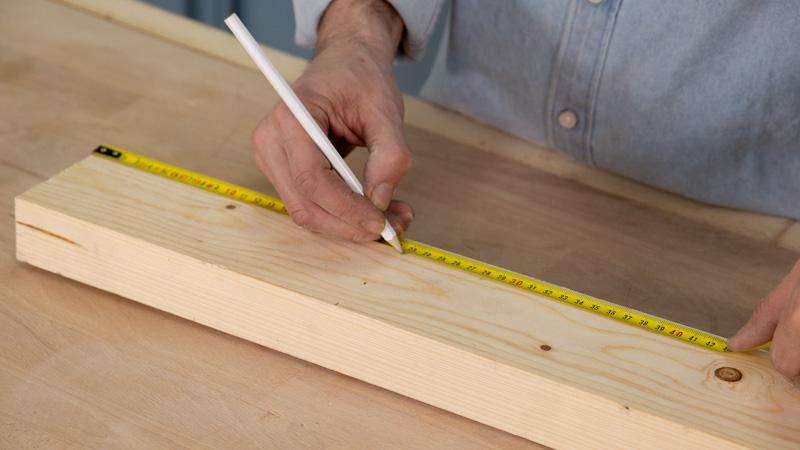 Lápiz marcando en la madera el poste interior de la estructura