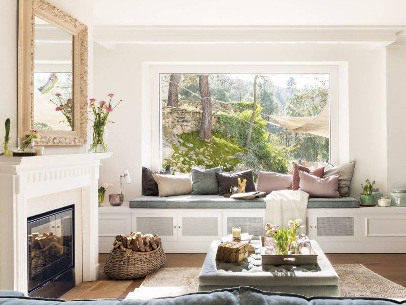 Salón amplio con gran ventanal y sofá de cojines debajo de la ventana.