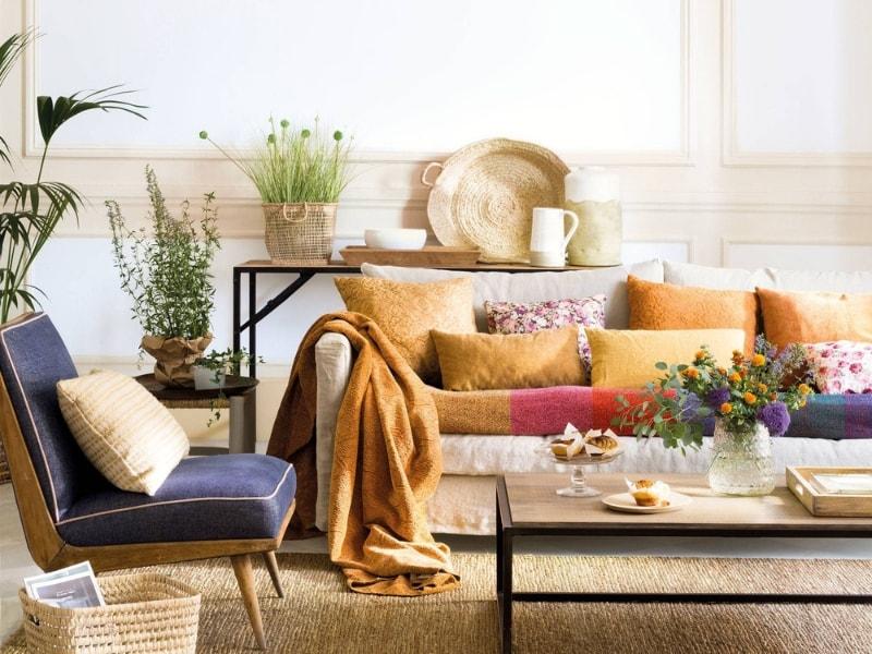 Decoración de salón con cojines de diferentes texturas y colores mostaza y amarillo.