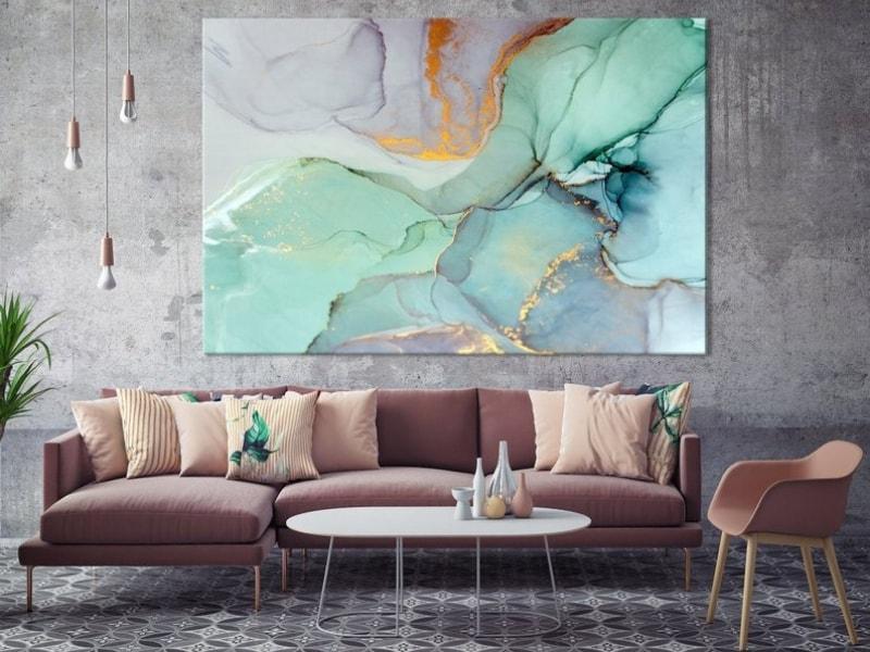 Decoración de salón con maxicuadro de tamaño XL con efecto marmolado de colores fríos y dorados en salón industrial.