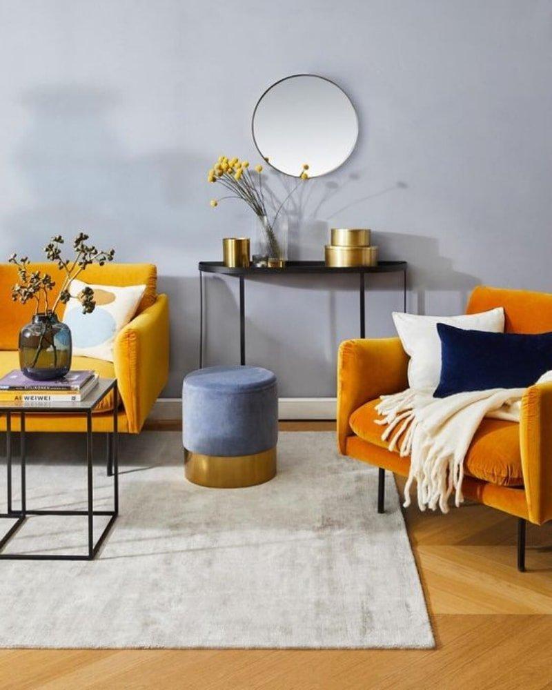 Salón con colores neutros y sofás de color amarillo mostaza