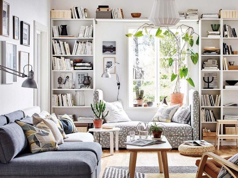 Salón en tonos grises con estanterías llenas de libros y ventana con luz natural para iluminar la zona de estar