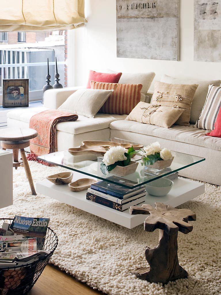 Decoración de salón de estar con una alfombra de pelo largo de color beige y mesa de centro de cristal.