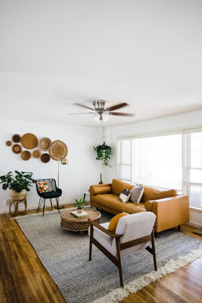 Salón rústico decorado con colores mostaza y terrosos. Paredes decoradas con elementos de mimbre y ventilador de madera.