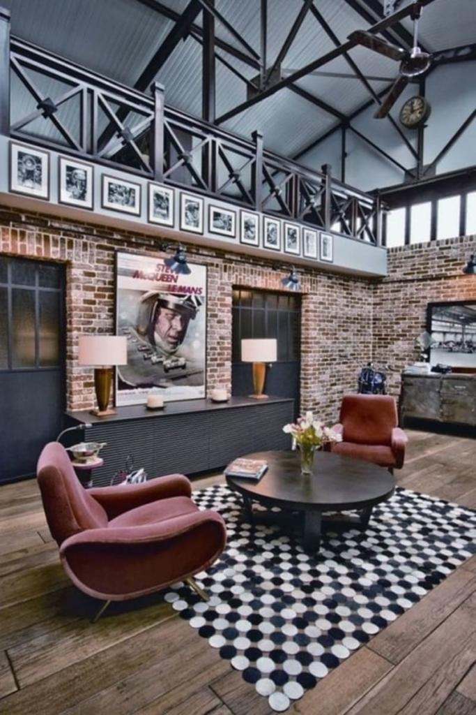 Estilo industrial en el salón de estar con aprovechando los elementos arquitectónicos del espacio como las vigas de hierro y los ventanales