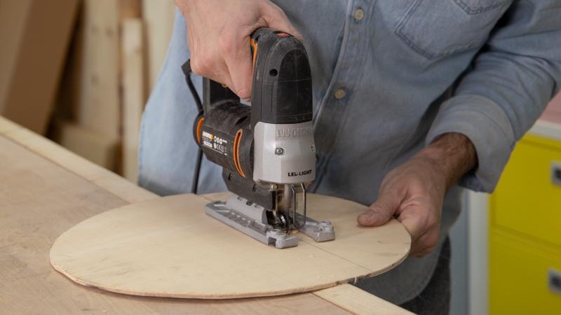 Sierra de calar cortando piezas de madera para crear la estructura interna del balancín infantil