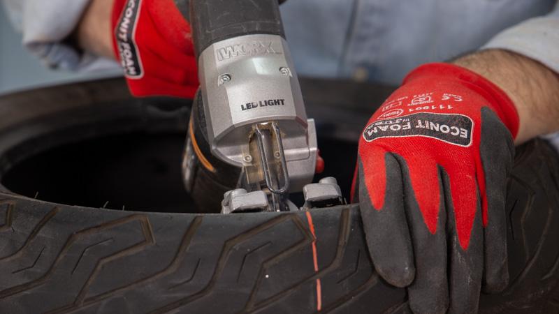 Sierra de calar cortando el neumático de moto para hacer un balancín casero