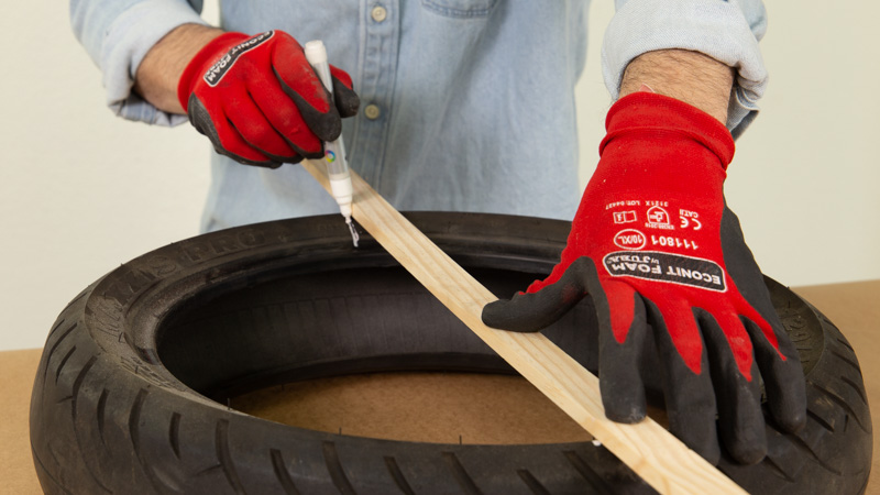 Utilización de un listón de madera para marcar la mitad del neumático
