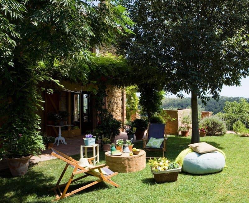 Jardín dividido en varias zonas con un merendero en la zona sombreada y una zona de confort y descanso en el jardín.