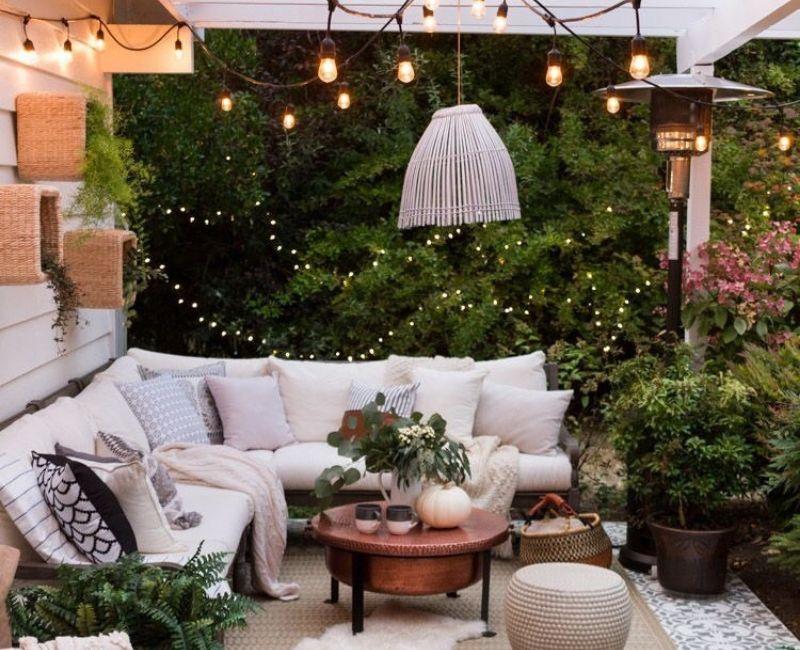Decoración de exterior para el jardín con luces y cojines para crear calidez.