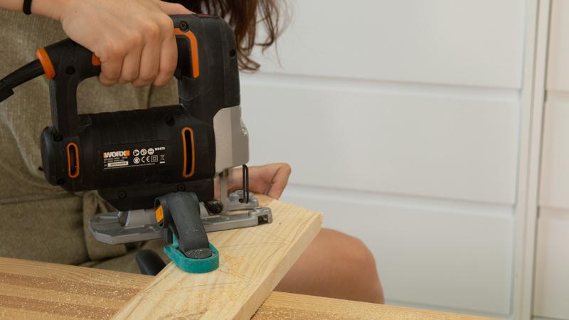 Sierra de calar cortando las piezas de madera de la maceta en forma de sol