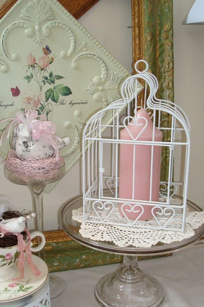 Jaula vintage de color blanco decorada con una vela de color rosa pastel