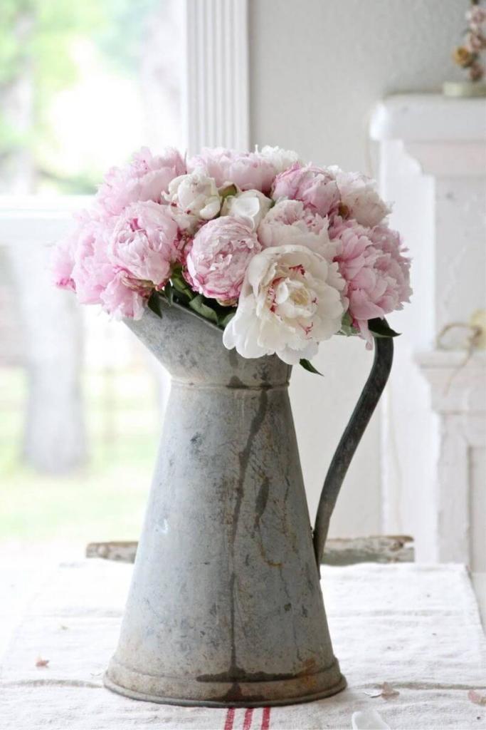 Ramo de peonías de color rosa y blanco en una jarra antigua de metal al más puro estilo shabby chic