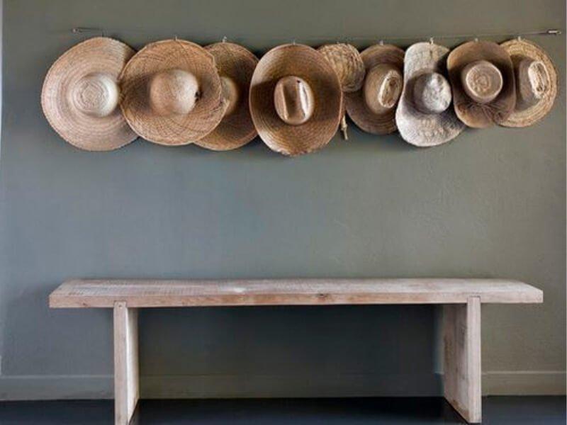 Decoración  de pared con sombreros de paja en una cuerda