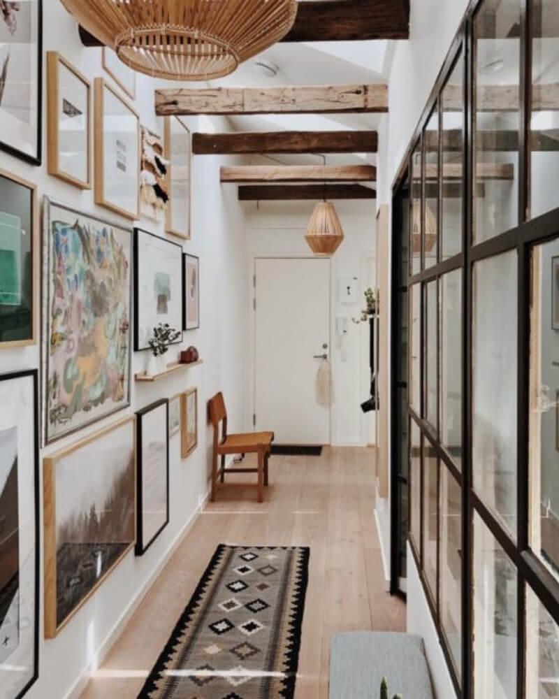 Decoraciónd e pasillo con vigas de madera en el techo, alfombra persa alagrada y marcos de fotos con ilustraciones