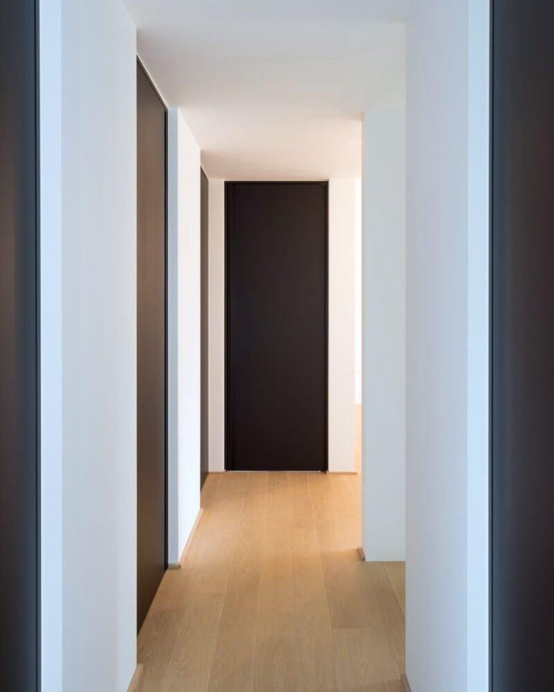 Decoración de pasillos con las paredes blancas y las puertas de color negro estilo minimalista