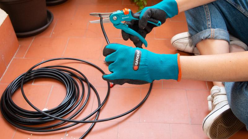 Tijeras cortando el tubo de distribución del riego por goteo