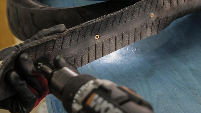 Atornillar varios tornillos al listón y al neumático