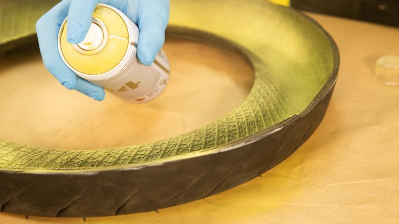 Aplicación de pintura en spray sobre la goma del neumático