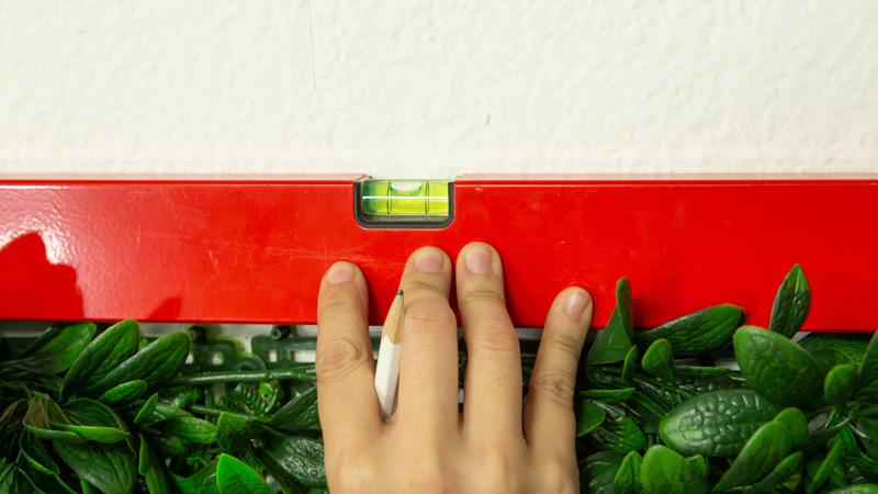 Comprobación de que el jardín vertical queda recto con la ayuda de un nivel