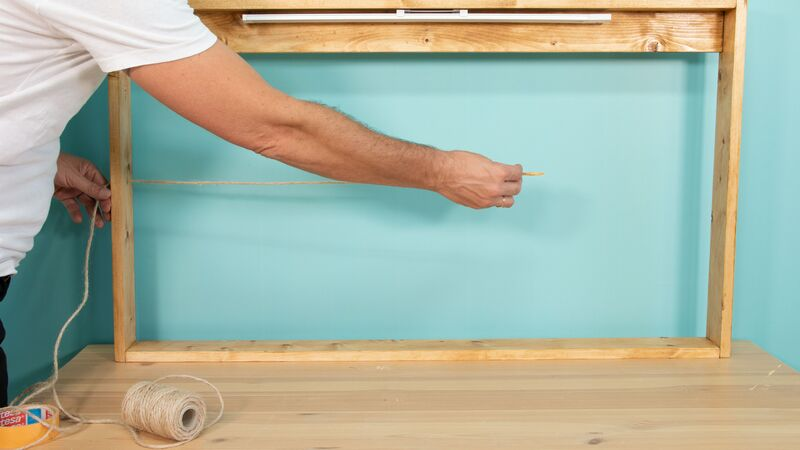 Colocación de la cuerda en los agujeros de las piezas laterales del mueble para colgar notas