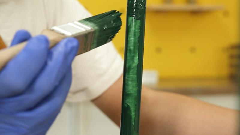 Aplicación de una segunda capa de pintura a las patas del taburete
