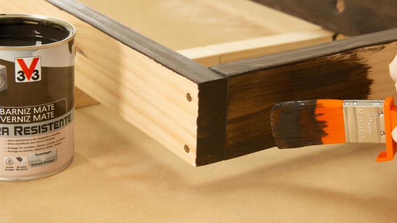 Aplicación de barniz sobre la estructura de madera
