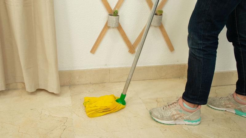 Aplicación de la mezcla sobre el suelo de mármol con la fregona, primer paso para renovar un suelo
