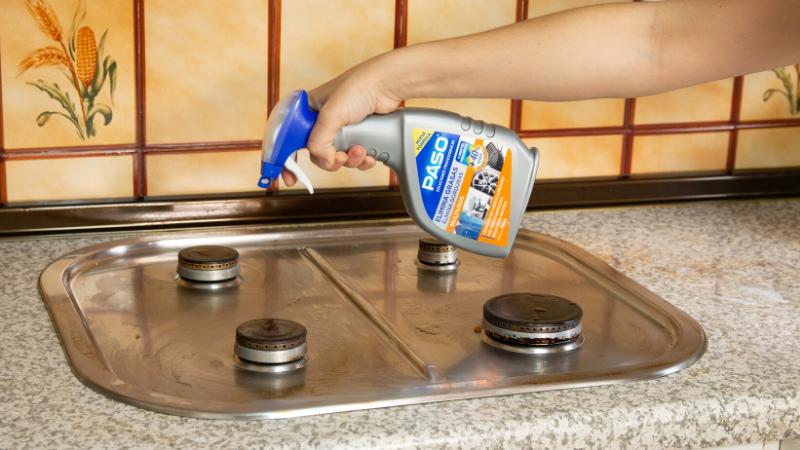 Aplicación del elimina grasas de PASO sobre la superficie que rodea los fuegos de la cocina