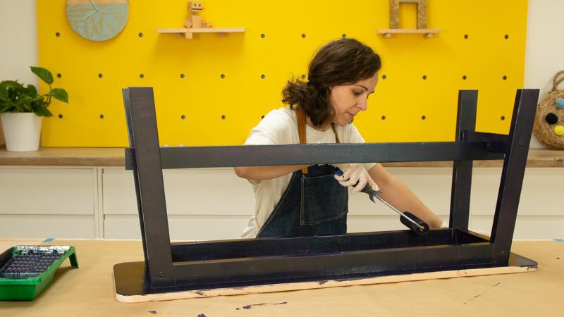 Aplicación de una segunda capa de pintura sobre el banco de madera