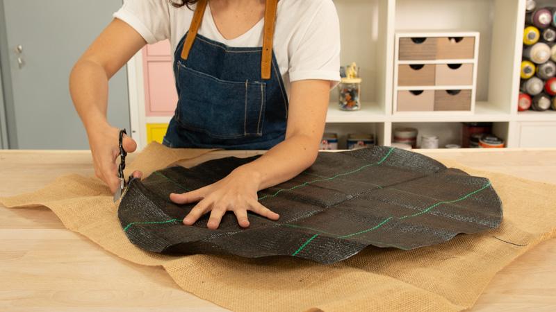 Corte de la tela de arpillera para recubrir la base