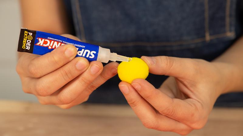 Applying adhesive on a pom pom