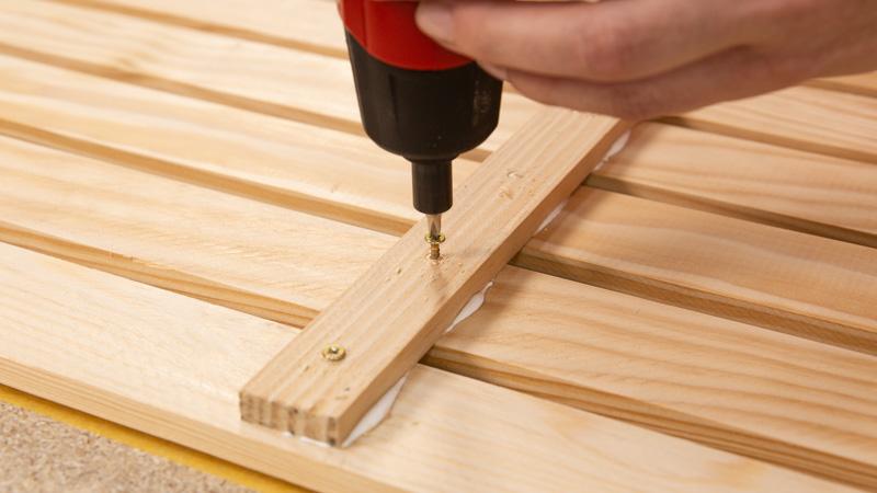 Atornillado de los travesaños a la madera, finalización de la estructura del organizador de herramientas