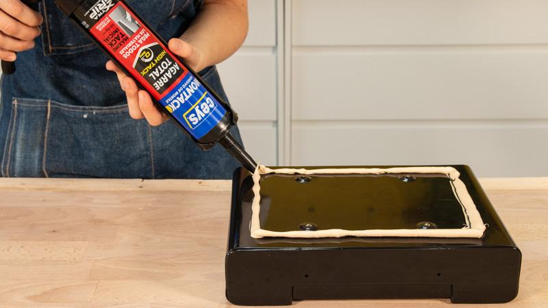 Aplicación de adhesivo de montaje sobre la base del buzón