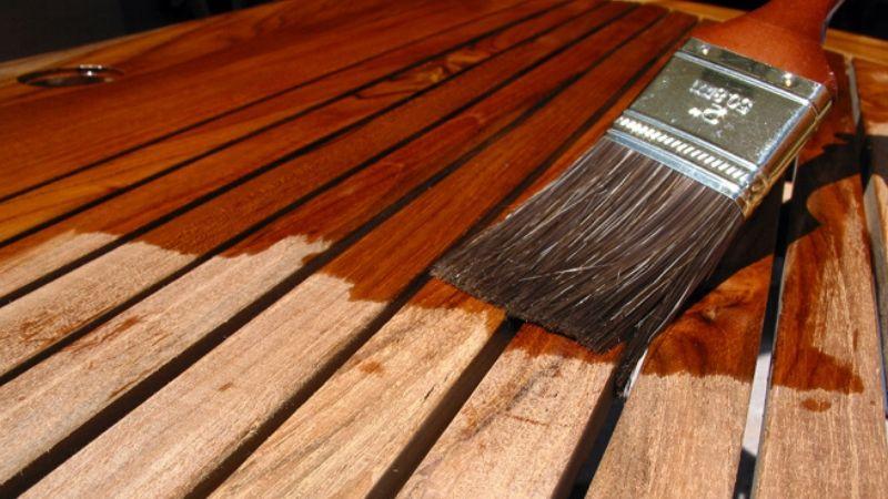 Barniz para madera con una brocha