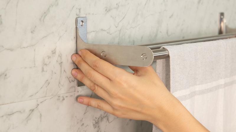Pegado de colgador de toallas a la pared con adhesivo de montaje