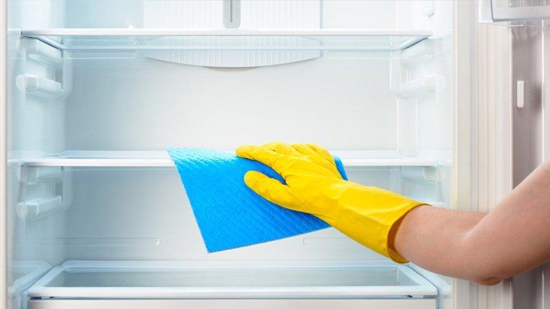 Persona limpia con una bayeta el interior de un frigorífico