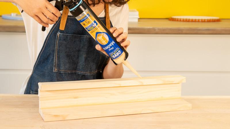 Aplicación del sellador sobre la estructura del estante para colocar cuadros