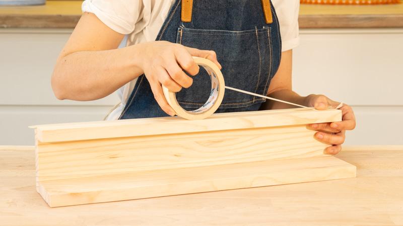 Colocación de cinta de carrocero alrededor de las juntas de la estructura del estante para poner cuadros
