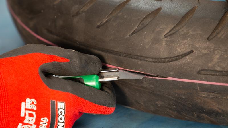Corte de la goma del neumático con un cúter