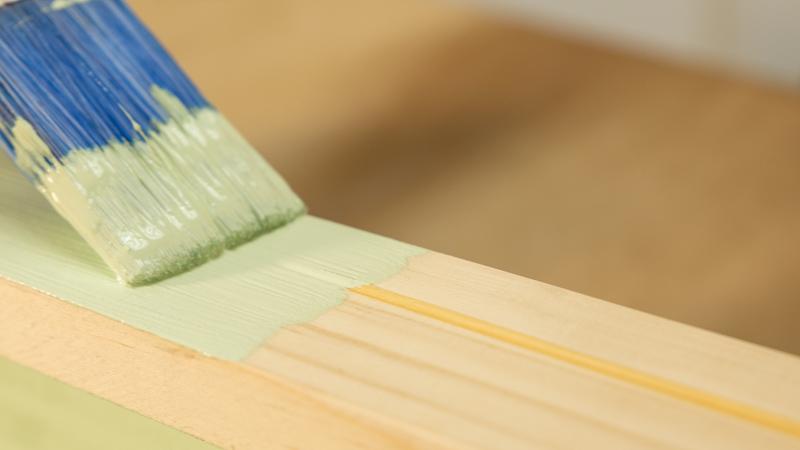 Aplicación de pintura sobre la madera del estante para poner cuadros