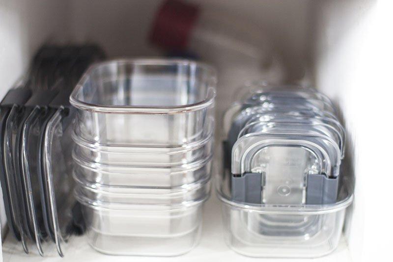 Tuppers de vidrio dentro de un armario bien organizados unos dentro de otros