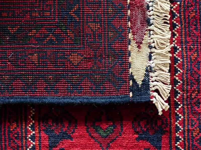 Detalle de alfombra clásica de lana de color rojo y azul marino