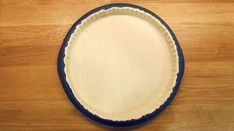 Masa de hojaldre cruda colocada en un molde de quiche de silicona azul oscuro